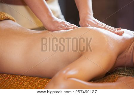 Woman Receiving Back Massage At Spa. Female Having Relaxing Massage On Her Back In Spa Salon.