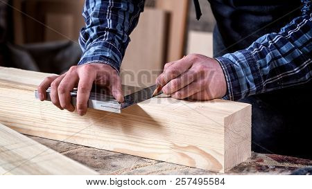 Close-up of craftsman hands in gloves measuring wooden plank with ruler and pencil on workbench. Concept of woodwork and handcraft. poster