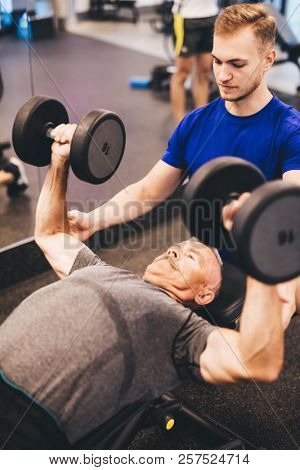 Personal trainer assisting older man in an exercise. Retirement activities. Health. poster