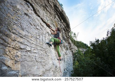 A Strong Girl Climbs The Rock. Training In Rock Climbing. The Climber Climbs The Rock. Exercise In N