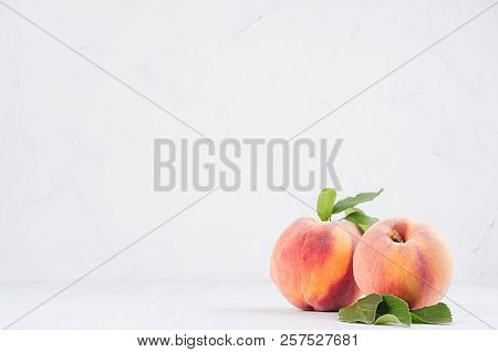 Elegance Ripe Peaches With Green Young Leaves On White Soft Wood Background, Copy Space.