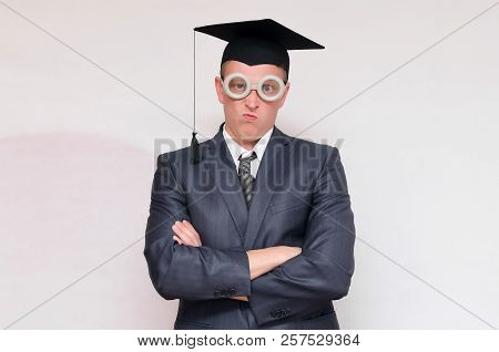 Disgruntled and arrogant graduate student in the cap isolated on gray background. Education concept. poster