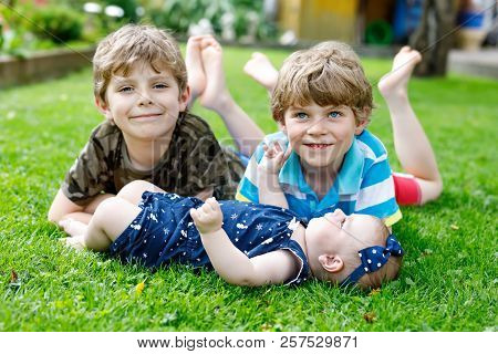 Two Little Happy Kid Boys With Newborn Baby Girl, Cute Sister. Siblings On Grass In Summer Or Spring