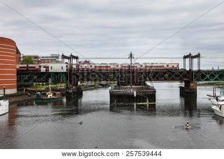 NORWALK, CONNECTICUT, USA - JUNE 20, 2015 : Maritime Aquarium and railroad bridge with train view from road bridge.