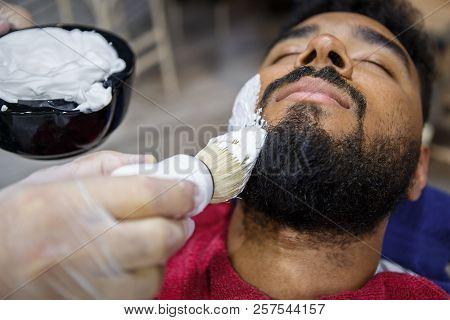 Young Black Man Shaving Beard In Barbershop
