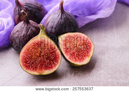 Fresh figs. Whole figs and sliced in half figs on stone table background with purple gauze fabric. poster