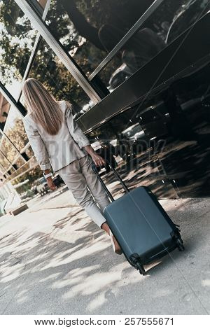Confident Businesswoman. Full Length Rear View Of Young Woman In Suit Pulling Luggage While Walking
