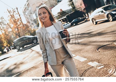 Young Business Professional. Beautiful Young Woman In Suit Pulling Luggage And Smiling While Walking
