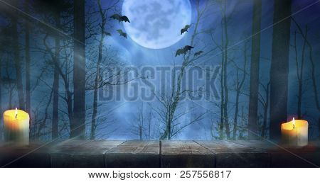 Halloween night scary autumn forest with wooden table background. Focus is on the table
