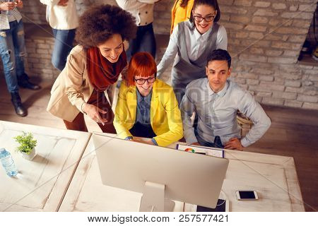Group of young people looking at computers screen in office