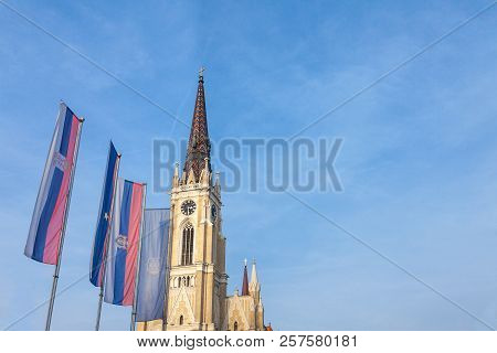 The Name Of Mary Church, Also Known As Novi Sad Catholic Cathedral On A Sunny Afternoon With The Fla