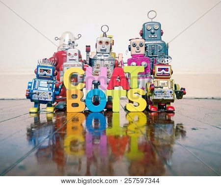 CHAT BOTS wooden letters and retro robot toys on a wooden floor with reflection