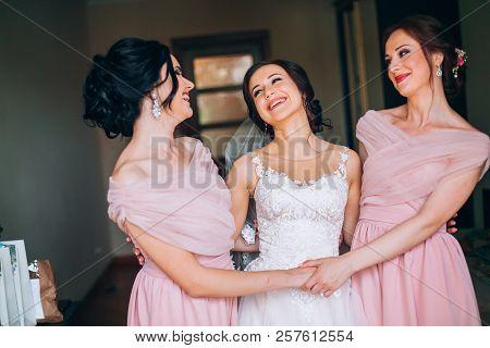 Wedding. Bridesmaid Preparing Bride For The Wedding Day. Bridesmaid Helps Fasten A Wedding Dress The