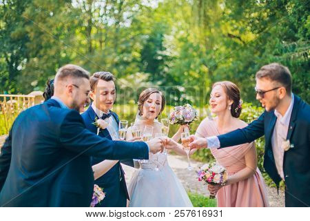 Bride and groom with happy groomsmen and bridesmaids having fun and popping champagne, newlyweds wedding hilarious moment. Funny momen. Crazy wedding people. poster