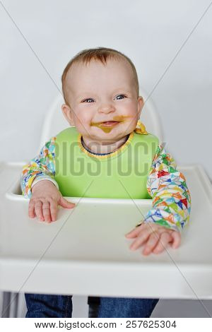 Funny Baby With Durty Face On The High Chair