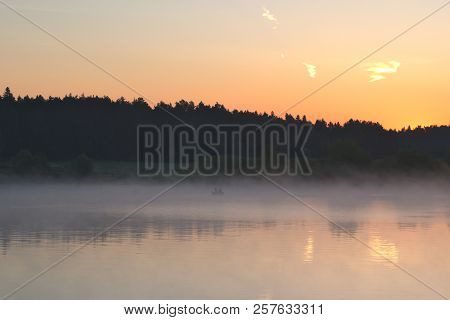 Boat With Fishermen In The Fog On The River At Dawn. Fishermen On A Boat Are Fishing At Dawn. The Ri