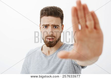 Concerned And Worried Handsome Young Male Friend With Blue Eyes, Beard And Moustache Pulling Palm To