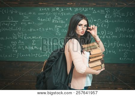 Student Excellent Accumulates Knowledge. Girl With Big Backpack Holds Pile Books, Chalkboard Backgro