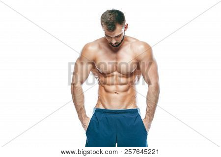 Bodybuilder Posing. Beautiful Sporty Guy Male Power. Fitness Muscled In Blue Shorts. On Isolated Whi