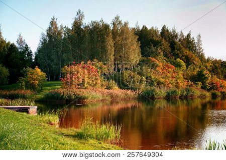 Fall Season Start Idyllic Lake Reflections Of Fall Foliage. Colorful Autumn Foliage Casts Its Reflec