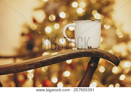 Mug With Hot Drink On Old Wooden Chair On Background Of Golden Beautiful Christmas Tree With Lights