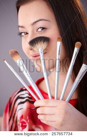 Beautiful young woman holding make-up brushes, looking at camera, smiling.