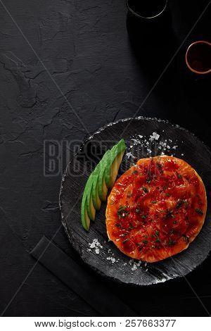 Top View Of Okonomiyaki, Traditional Japanese Savory Pancake With Sliced Avocado And Fish With Sauce