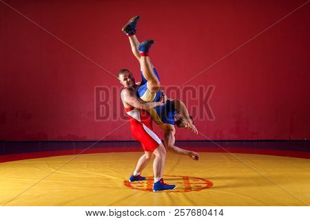 Two greco-roman  wrestlers in red and blue uniform wrestling  on a yellow wrestling carpet in the gym. Young man grappling poster