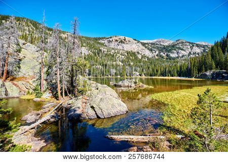 Lone Pine Lake with rocks and mountains around at autumn. Rocky Mountain National Park in Colorado, USA.