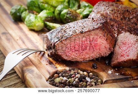 Cut Steak With Vegetables On Wooden Desk