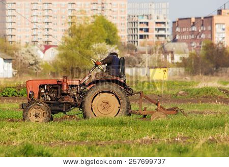 A Tractor Driver Plowing Soil In Autumn To Sow Winter Wheat. Side View Of A Tractor Driver On Tracto