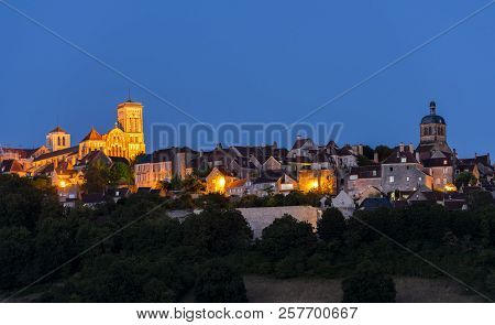 The UNESCO village of Vezelay on a hill with the Benedictine abbey and church of Saint Mary Magdalene at night in Yonne, France. poster