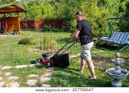 Gardener With Electric Lawn Mower Is Trimming The Garden. Sunny Day, Dacha. Adult Man Pruning And La