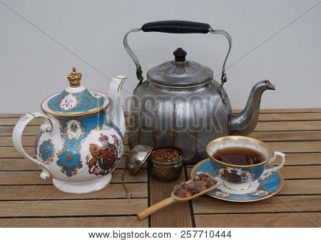 Nostalgic water kettle with english teapot, english tea cup, filled tea infuser and candy poster