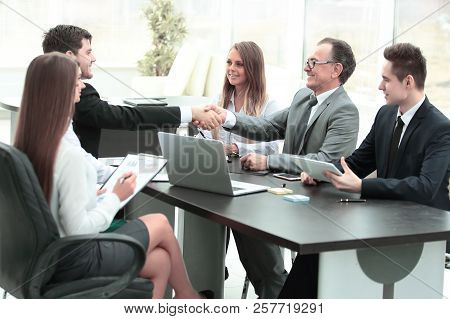 Handshake Of Business Partners At The Negotiating Table