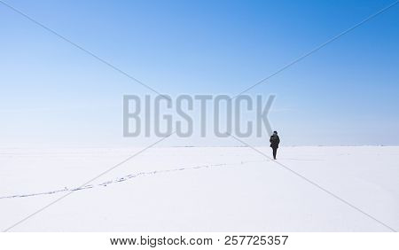Lonely Girl Walks Along The Endless Snowfield