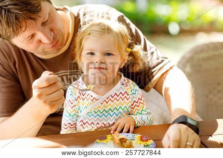 Young Middle-aged Father Feeding Cute Little Toddler Girl In Restaurant. Adorable Baby Child Learnin