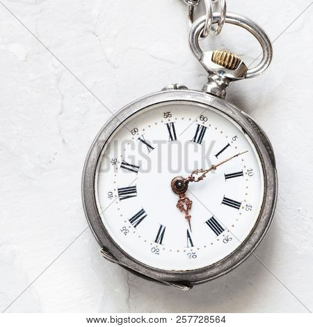 Used Silver Pocket Watch On Light Gray Plaster Background