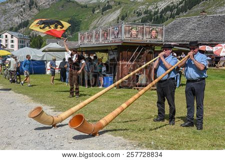 People Playing The Alphorn And Flag Bearers At Engstlenalp, Switzerland