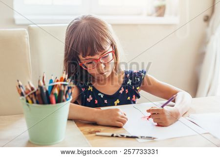 Child wearing glasses draws by left hand with color pencils at the table in room
