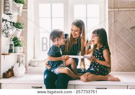Mom with her two children sitting on the kitchen table and eating candies. Mother with daughter and toddler son having breakfast at home. Happy lifestyle family moments.