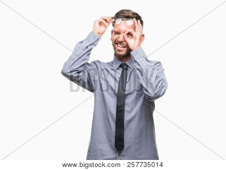 Young handsome business man over isolated background doing ok gesture with hand smiling, eye looking through fingers with happy face.