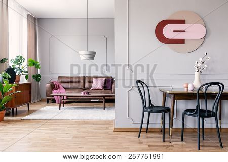 Real Photo Of Open Space Living Room Interior With Modern Clock On Wall With Molding, Table With Bla