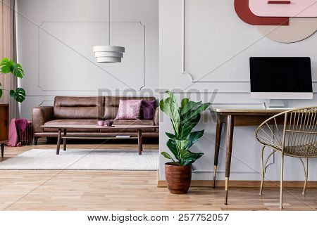 Gold Chair At Desk With Desktop Computer In Open Space Interior With Plant And Sofa. Real Photo
