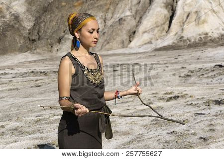 Young Woman Of Oriental Appearance In Clothes In Folk Style Searches For Water In A Desert Area By T