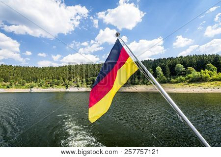 German Flag On A Boat In The Summer Waving In The Wind Over A Lake