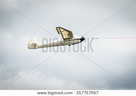 Small Glider Airplane With A Line Dragged Into The Air
