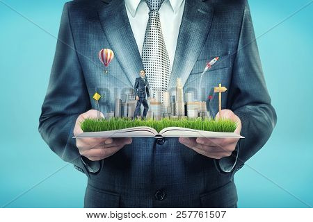 A Giant Businessman Holds An Open Book That Also Holds A Tiny Businessman Standing On A Field Near S