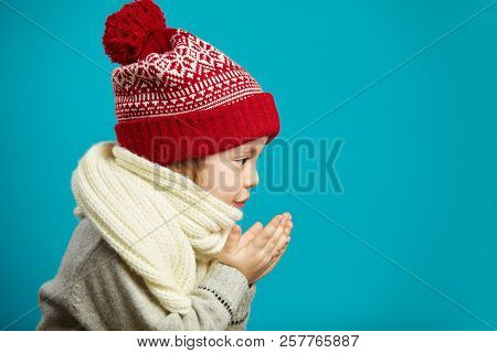 Profile Portrait Of Little Girl In Red Christmas Hat, Folded Her Hands Together And Blowing Sideways