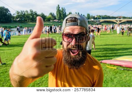 Man cheerful face shows thumb up. Man bearded in front of crowd riverside background. Top list summer festival must visit. Hipster visiting event picnic fest or festival. Highly recommend top list poster